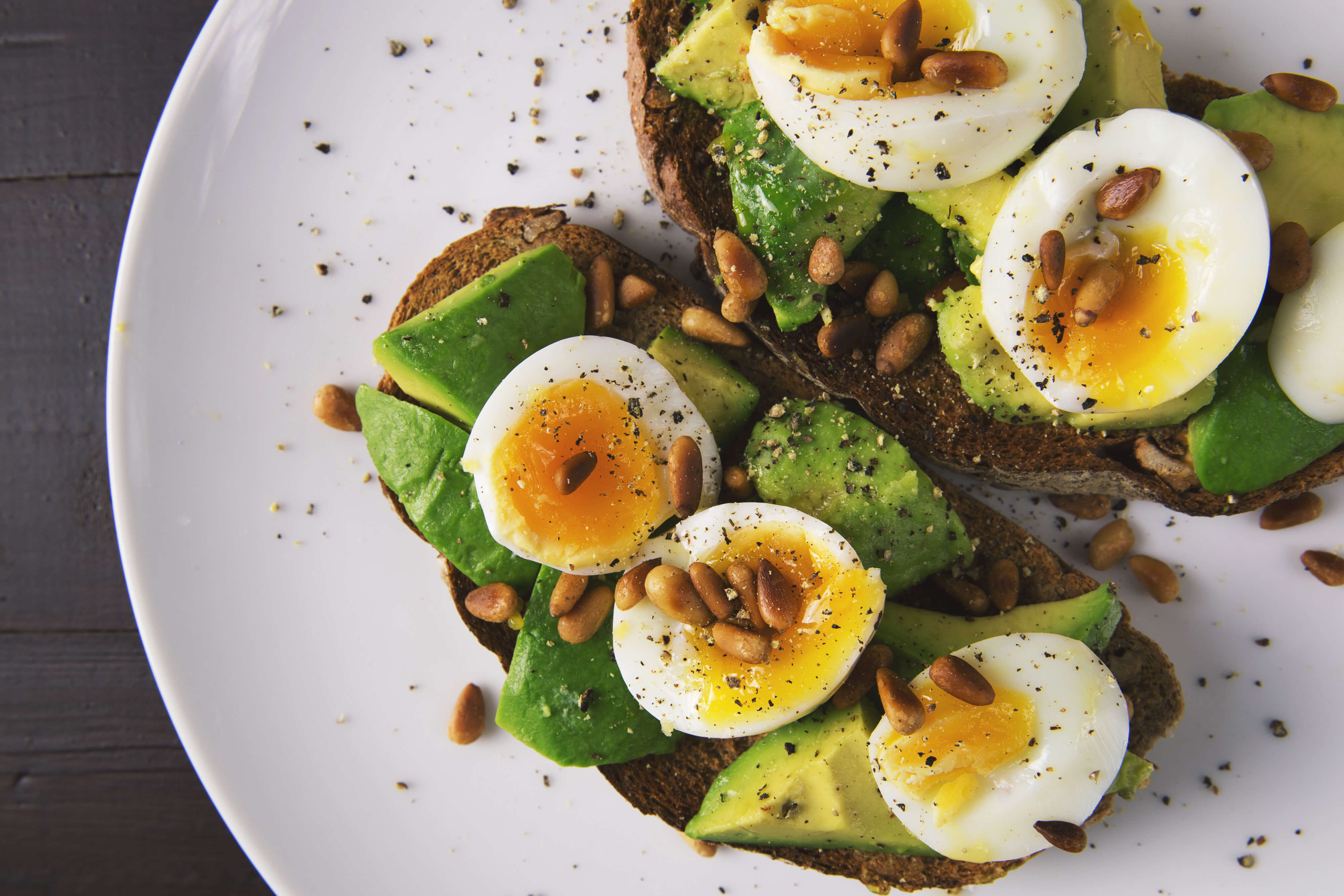 Eggs and avocado on toasted bread with pine nuts image